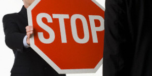 Man holding stop sign in front of another man